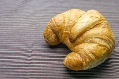 Croissant on Tablecloth. Fresh and tasty croissant on brown Tablecloth Stock Image