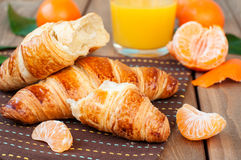 Croissant and tangerines Stock Images