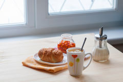 Croissant with tea and jam. Tea with croissant and sea buckthorn jam Royalty Free Stock Photos