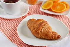 Croissant with tea and orange for breakfast Stock Images
