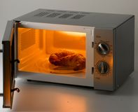 Croissant in un forno a microonde aperto fotografia stock