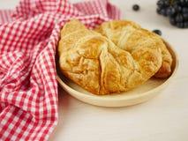 Croissant vicino su sulla tavola di legno beige immagine stock