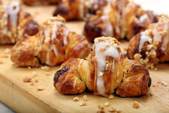 Croissant with walnuts on wooden background Stock Photos