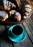 Croissant and white cup of black coffee on brown canvas. Stock Image