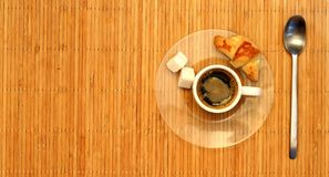 Croissant and a white cup of coffee on a plate stock photography