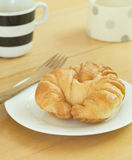 Croissant on white plate and cupof coffee. Royalty Free Stock Photos