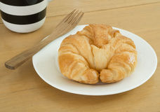 Croissant on white plate and cupof coffee. Stock Photos