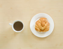 Croissant on white plate and cupof coffee. Stock Image