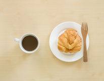 Croissant on white plate and cupof coffee. Stock Photography