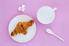 Croissant on a white plate and pink background. Top view. place for text labels. set for breakfast Royalty Free Stock Photography