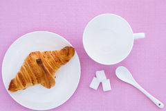 Croissant on a white plate and pink background. Top view. place for text labels. set for breakfast Stock Photos
