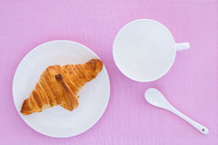 Croissant on a white plate and pink background. Top view. place for text labels. set for breakfast Stock Images