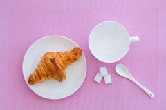 Croissant on a white plate and pink background. Top view. place for text labels. set for breakfast Royalty Free Stock Image
