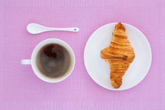 Croissant on a white plate and pink background. Top view. place for text labels. set for breakfast Royalty Free Stock Photo