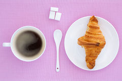 Croissant on a white plate and pink background. Top view. place for text labels. set for breakfast Stock Photo