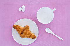 Croissant on a white plate and pink background. Top view. place for text labels. set for breakfast Stock Image