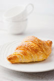 Croissant on the white plate with two blurred cups Stock Images