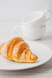 Croissant on the white plate with two blurred cups vertical Stock Images