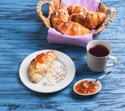 Croissant in a wicker basket. Breakfast Three croissant in a wicker basket on a purple cloth, a croissant on a white porcelain plate, sprinkled with almond stock photos