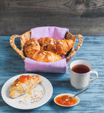 Croissant in a wicker basket. Breakfast Three croissant in a wicker basket on a purple cloth, a croissant on a white porcelain plate, sprinkled with almond royalty free stock photos