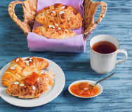 Croissant in a wicker basket. Breakfast Three croissant in a wicker basket on a purple cloth, a croissant on a white porcelain plate, sprinkled with almond stock photography