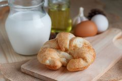Croissant on wooden cut board on table wood and fabric select focus shallow depth of field stock photography