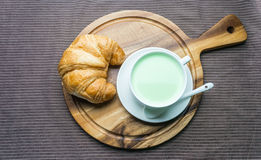 Croissant on woonden plate. Fresh and tasty croissant on woonden plate with green tea milk Royalty Free Stock Images
