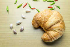 Croissant on woonden table. Fresh and tasty croissant on woonden table with chilli Pepper and garlic Stock Photos