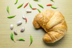 Croissant on woonden table. Fresh and tasty croissant on woonden table with chilli Pepper and garlic Royalty Free Stock Image