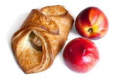 Croissant y aislamiento rojo de los melocotones en blanco Imagenes de archivo
