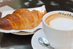 Croissant y Cappuccino para el desayuno fotografía de archivo