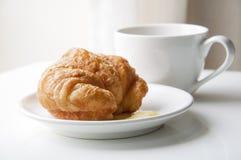 Croissant y taza de café Fotos de archivo libres de regalías