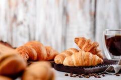 Croissants στα ξύλινα πιάτα με τον καφέ σε ένα ελαφρύ υπόβαθρο Στοκ φωτογραφίες με δικαίωμα ελεύθερης χρήσης