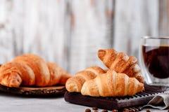 Croissants στα ξύλινα πιάτα με τον καφέ σε ένα ελαφρύ υπόβαθρο Στοκ φωτογραφία με δικαίωμα ελεύθερης χρήσης