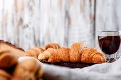 Croissants στα ξύλινα πιάτα με τον καφέ σε ένα ελαφρύ υπόβαθρο Στοκ Φωτογραφίες