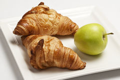Croissants and apple for breakfast. Two croissants and one apple on a white plate Stock Image