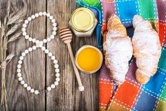 Croissants avec du miel pour le petit déjeuner le 8 mars Image stock