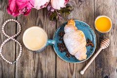 Croissants avec du miel pour le petit déjeuner le 8 mars Images stock