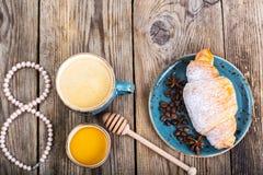 Croissants avec du miel pour le petit déjeuner le 8 mars Image libre de droits