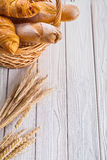 Croissants and baguettes in wicker basket ears of Stock Images