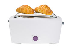 Croissants are baked in a toaster. Stock Photos