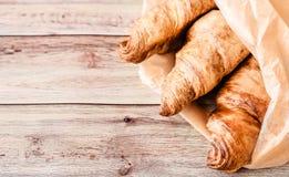 Croissants in bakseldocument worden verpakt op houten lijst die Hoogste mening royalty-vrije stock foto