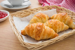 Croissants in basket with jam and coffee cup Stock Photo