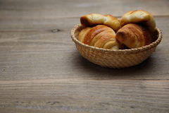 Croissants in the basket on wooden table Royalty Free Stock Photos