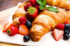 croissants with berries on wooden background Stock Image