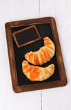 Croissants on a black board over white wooden background. Two croissants on a black board over white wooden background royalty free stock photography