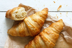 Croissants on brown bag on rustic white wood from above. Stock Photo