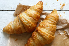 Croissants on brown bag on rustic white wood from above. Royalty Free Stock Photos