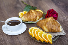 Croissants with butter ,cup of coffee and orange  for breakfast Stock Photos