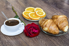 Croissants with butter ,cup of coffee and orange  for breakfast Stock Images